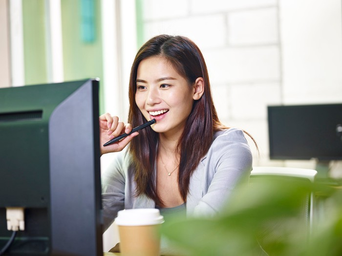 Smiling young female adult at computer