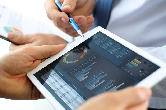 Person pointing to tablet with charts on the screen.