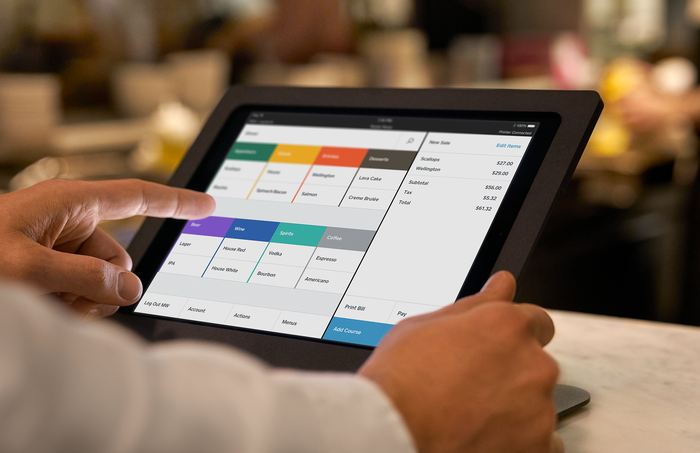 A restaurant employee interacts with the Square for Restaurants platform.