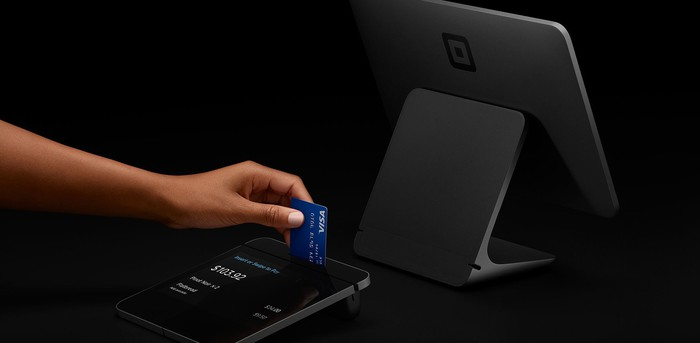 A customer uses a chip reader built into Square Register.