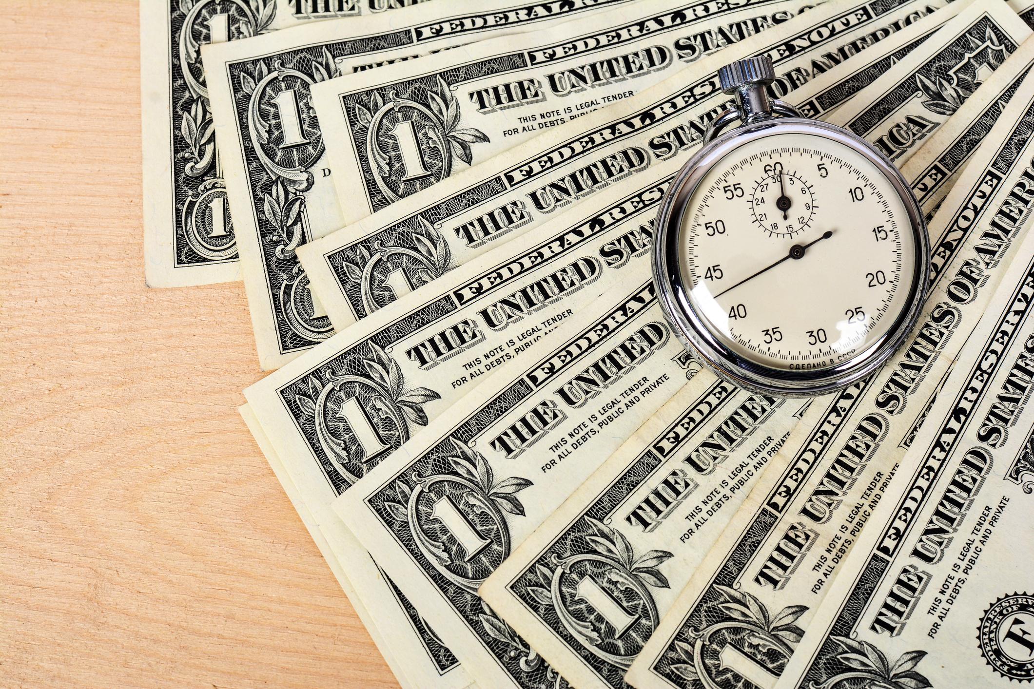 Dollar bills underneath a stopwatch