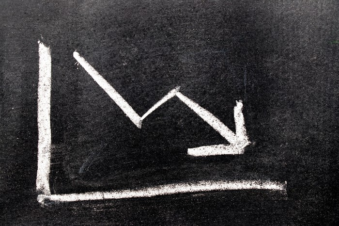 A chalkboard drawing of an arrow headed down.