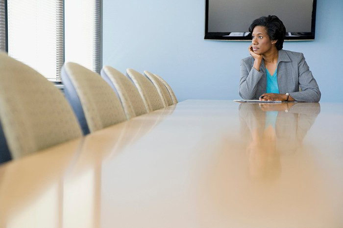 A woman sits at a conference room table and looks out the window with her chin resting on her hand.