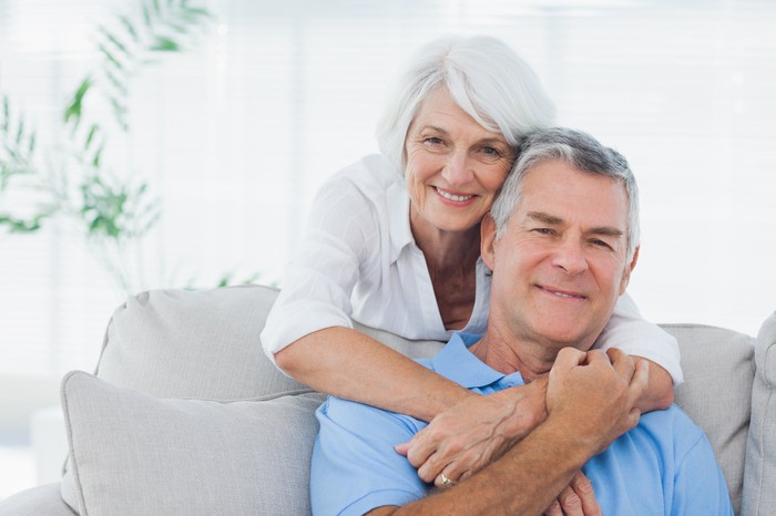 Older couple smiling on a couch.
