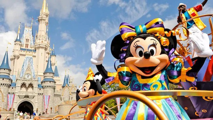 Minnie Mouse and Mickey Mouse waving with Cinderella Castle in background.