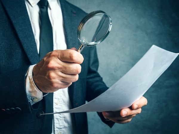 BUsiness man using magnifying glass at piece of paper