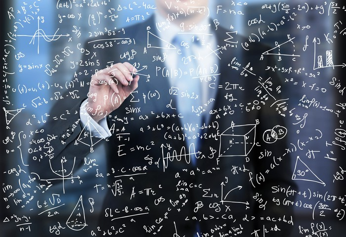 A man in a suit does financial calculations on a glass wall in the foreground.