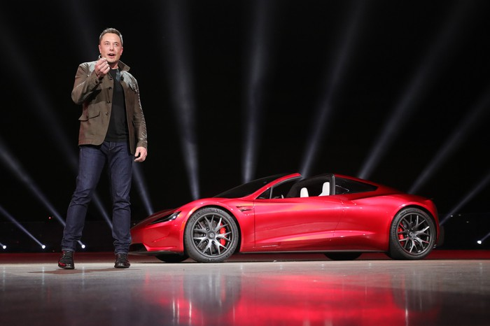 Elon Musk standing in front of the new Tesla Roadster