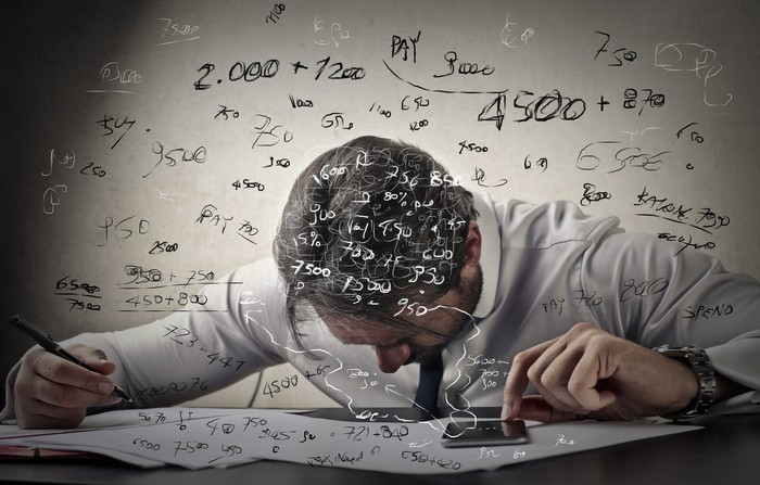 A man with his head down as mathematical formulas float above his head.