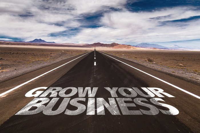 The words grow your business written on an open road