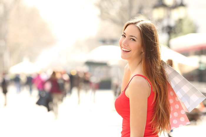 Smiling young woman brandishes several shopping bags on a sun-soaked city street.