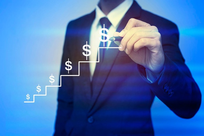 Dollar signs climbing up steps with a man in a suit and tie standing in the background.