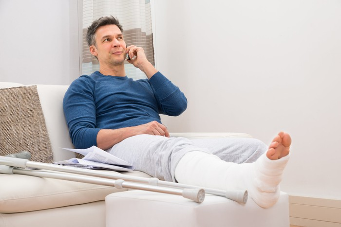Man with broken leg in cast sitting on couch talking on phone.