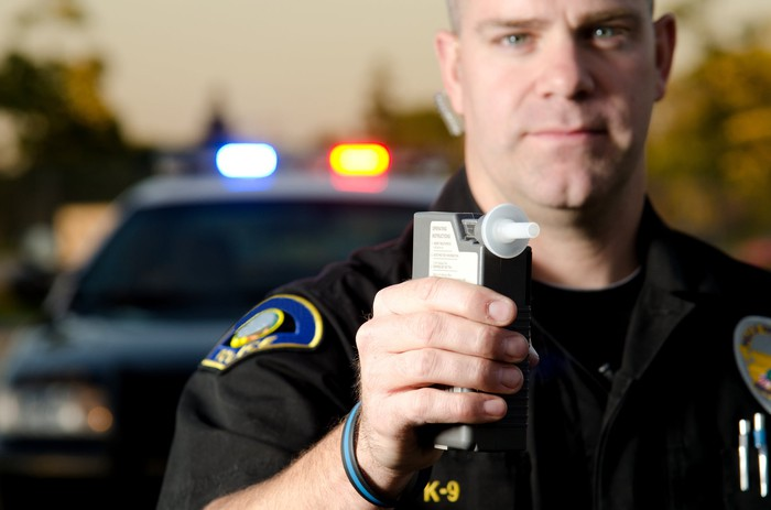 A law enforcement officer holding a breathalyzer device in his right hand, with his patrol vehicle in the background.