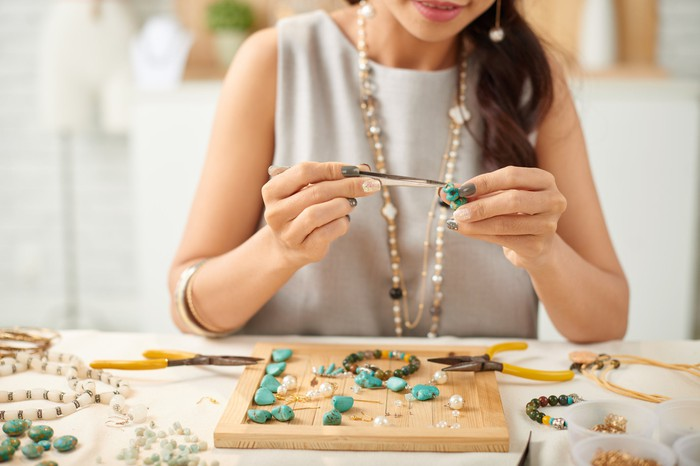 A woman makes bead necklaces.