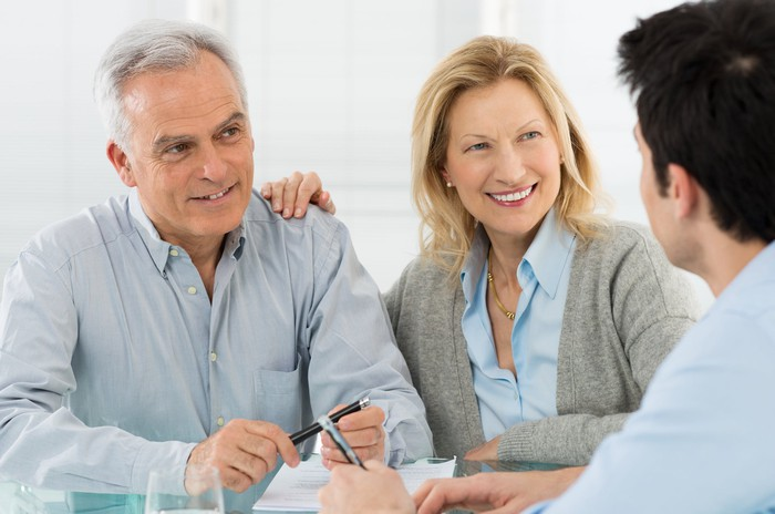 An older couple talking to a younger man across a table.