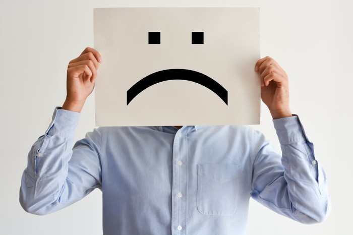 A person holds up a frowny-face sign over their face.
