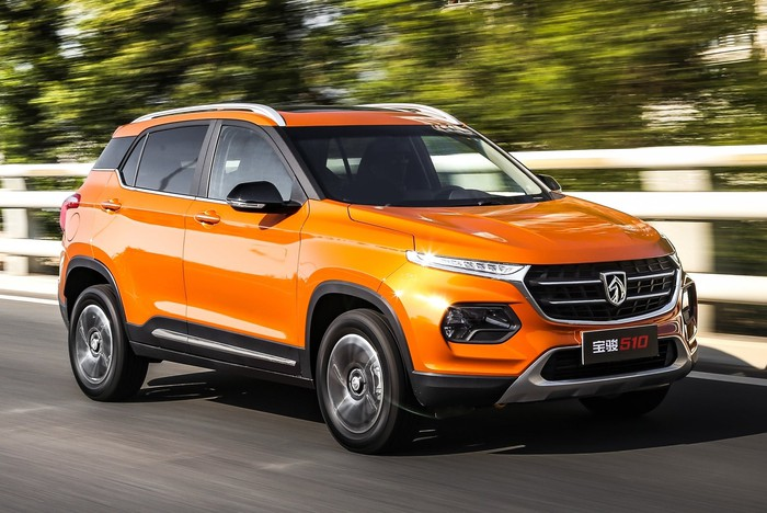 An orange Baojun 510, a compact SUV, at speed on a country road.