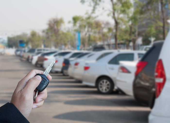 A hand holding a car key in the foreground, a row of vehicles at an auto dealership in the background.