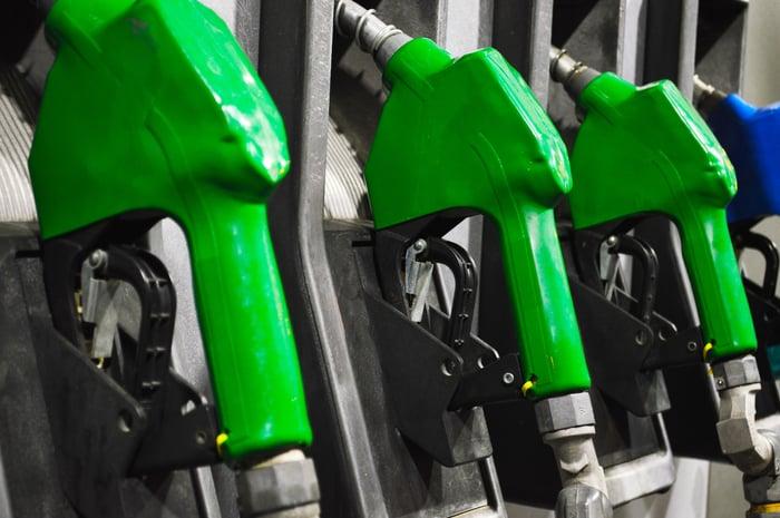 Three green diesel pump nozzles at a fuel station.
