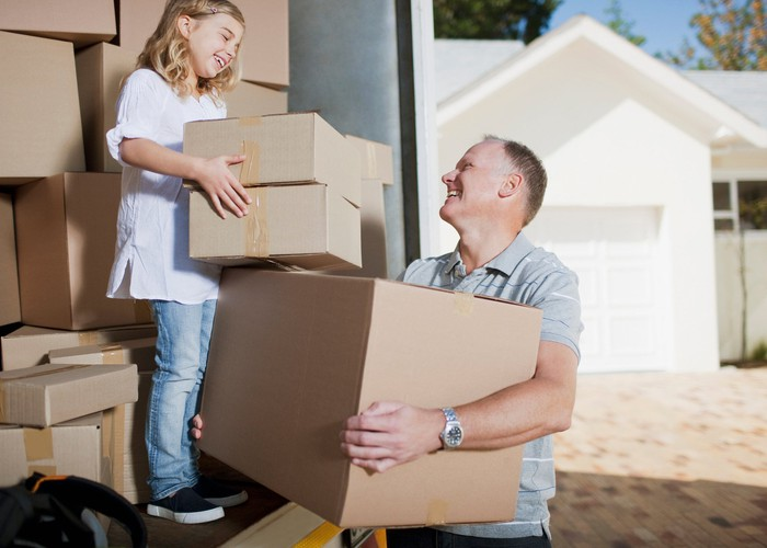 Middle-aged man and young girl carrying boxes from the back of a moving truck with a house in the background.