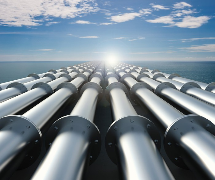 Pipelines going over a blue sea and with a blue sky ahead.