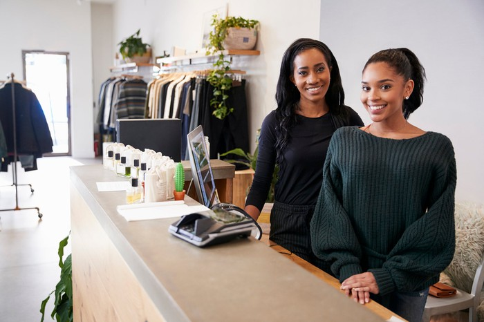 Two women are behind a counter at a clothing store.