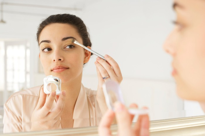 A woman applying makeup in a mirror.