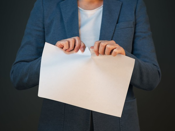 Business woman tearing up a piece of paper