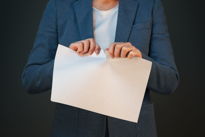 A person in a sportcoat is tearing a piece of paper.