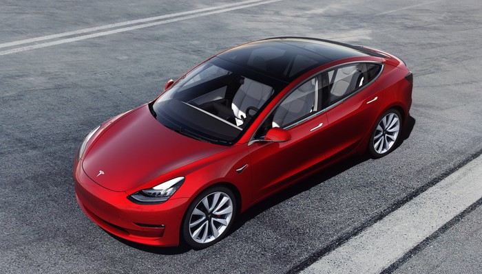 A red Tesla Model 3 Performance, a sleek high-performance compact luxury sedan, viewed from above.
