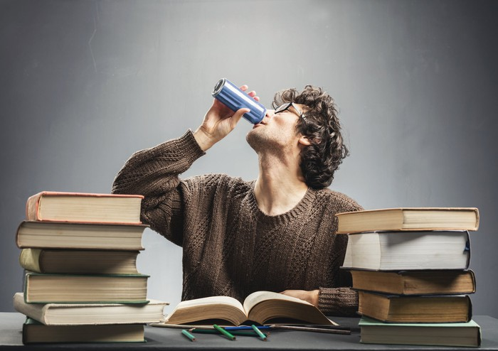 Student surround by books and drinking an energy drink.