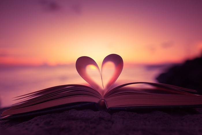Pages of a book folded inward to form a heart with sunset in the background.