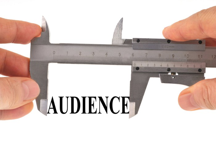 "Abstract concept of audience measurement: A pair of calipers measuring the word ""audience."""