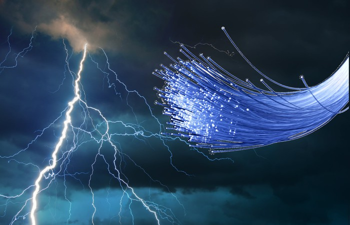 A bundle of fiber-optic networking cables against a backdrop of lightning bolts and dark clouds.