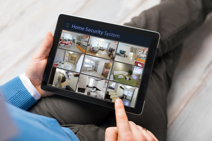 Man sitting on couch with tablet showing security camera views.