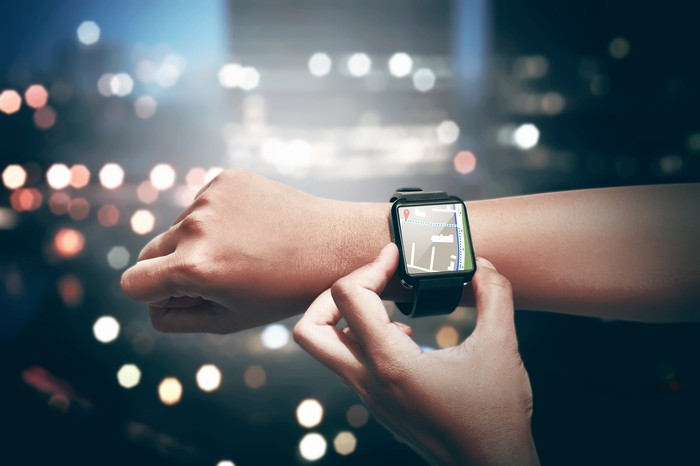 A woman checks her smartwatch.