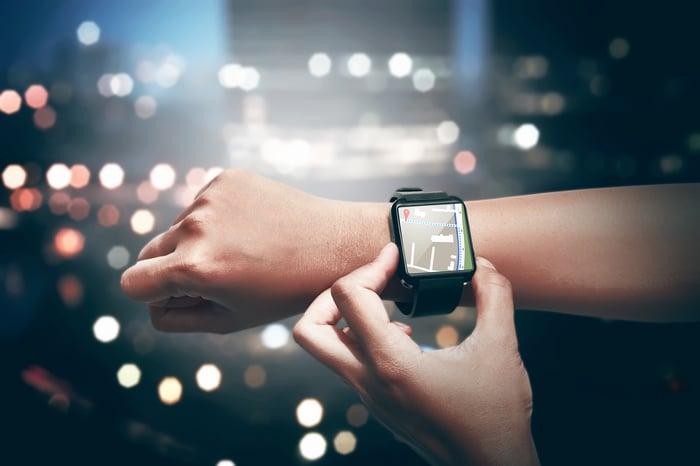 A woman checks her smartwatch.