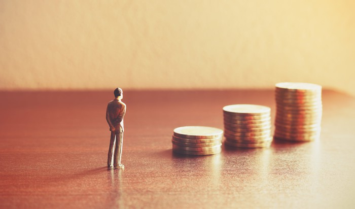 A tiny man looks at a growing pile of coins.