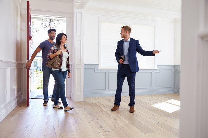 A real estate agent showing a home to a couple.
