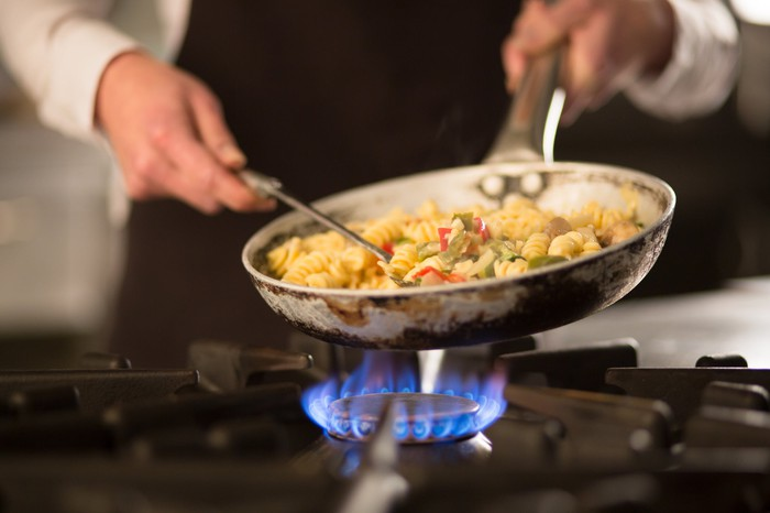 Chef cooking pasta on a commercial range