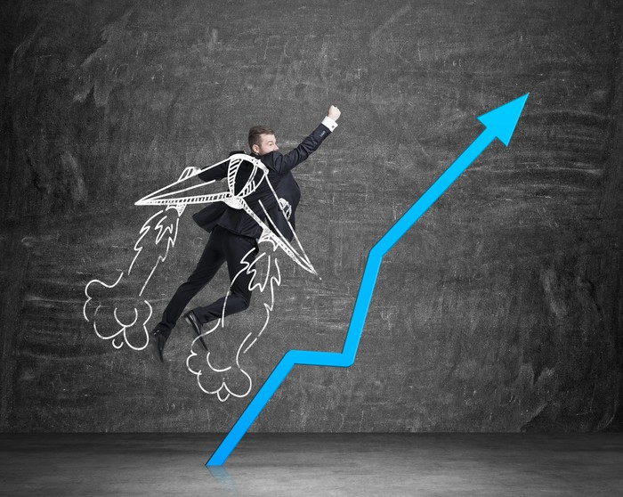 Soaring businessman with superimposed drawing of wings and jet exhaust over him next to blue line trending upward.