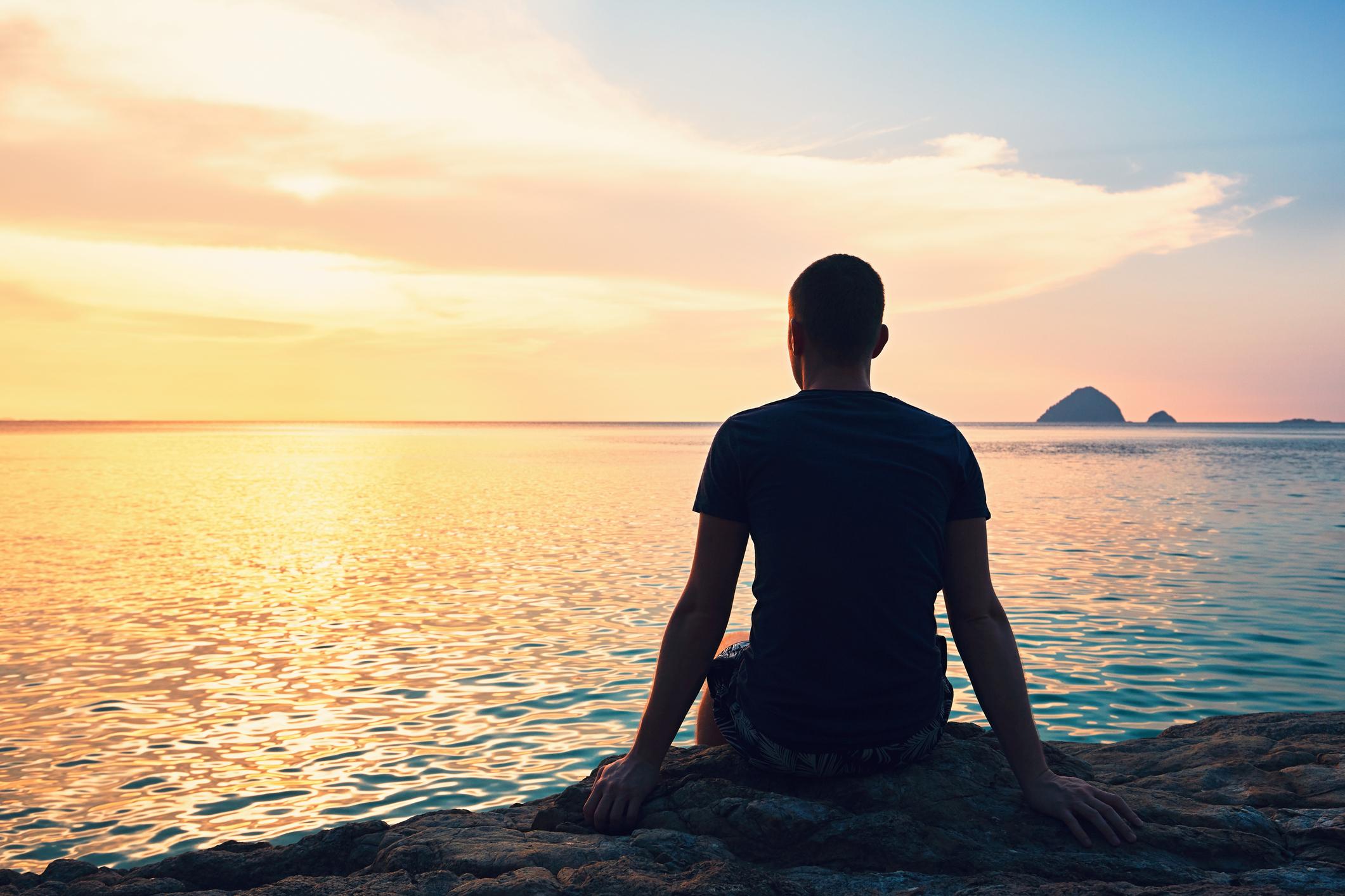 Man sitting facing the water at sunset