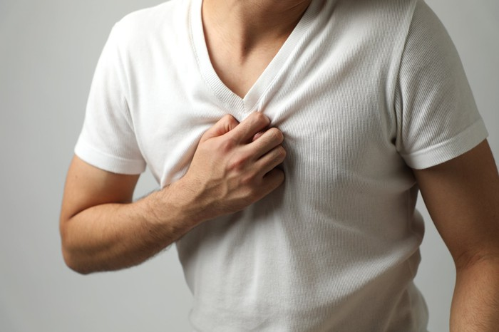 Man in a white v-neck shirt clutching his chest