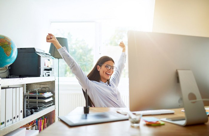 Woman smiling and raising her hands from behind a desk.