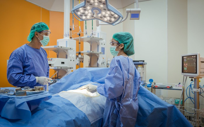 Doctors performing surgery with equipment in the background