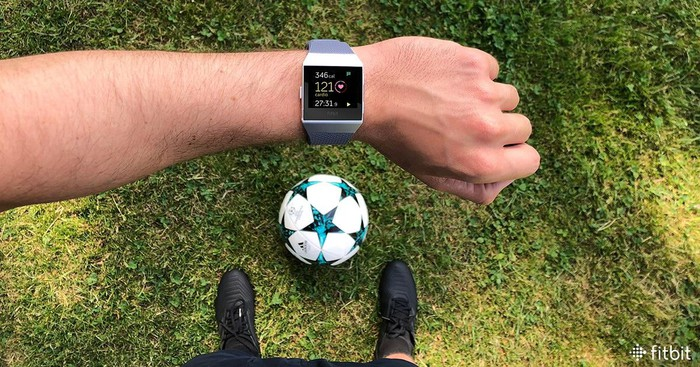 Man wearing a Fitbit device and standing over a soccer ball.