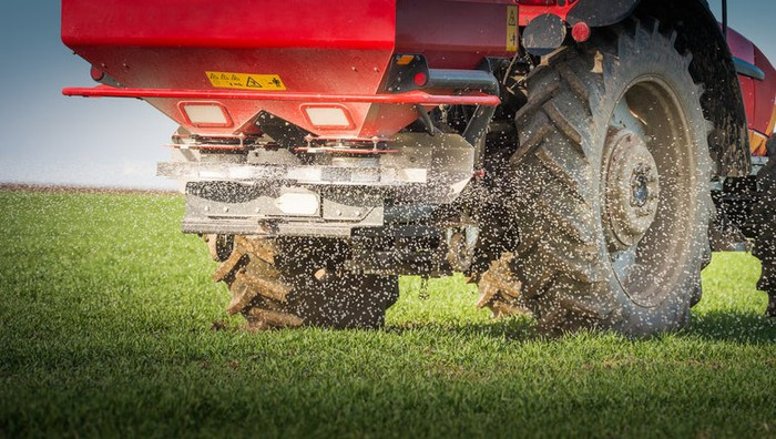 A tractor spreading fertilizer on a field.
