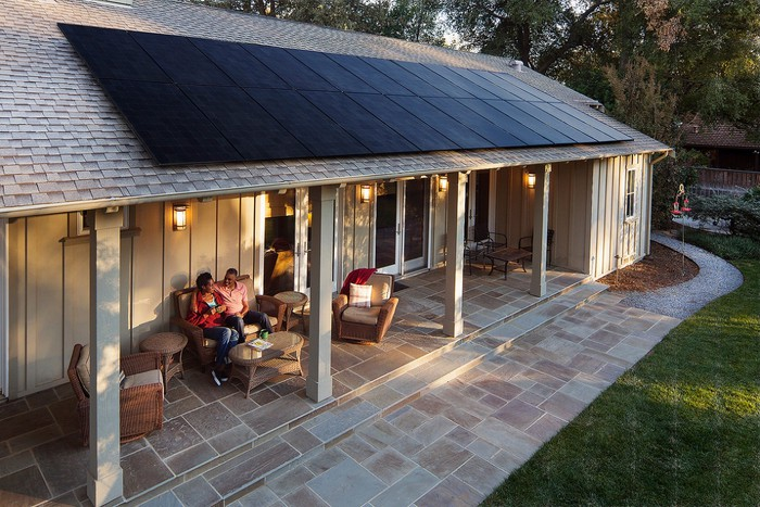 A home with solar panels on the roof and two people sitting under a covered patio.