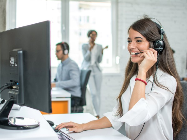 smiling woman with headset at computer_GettyImages-946991350